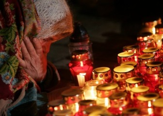 An elderly woman cries near the candles at a monument to Holodomor victims in central Kiev